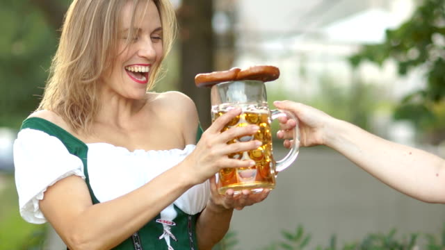 Girl-in-a-traditional-Bavarian-dress-takes-a-glass-of-beer-from-the-barman-at-the-beer-festival-Oktoberfest-The-woman-is-happy-and-laughs-she-is-surprised-and-cheerful-On-open-air