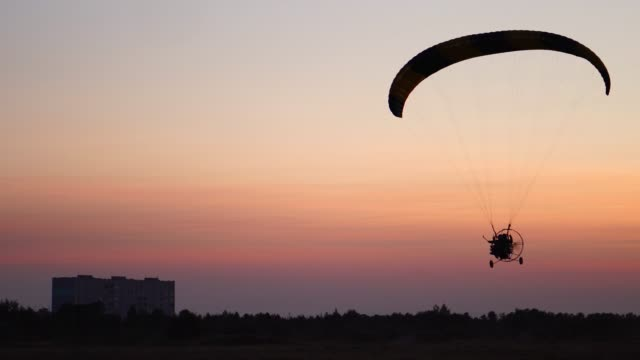 The-pilot-on-a-paraglider-flies-from-the-camera-gradually-moving-away-into-the-distance-against-the-sunset-beautiful-sky