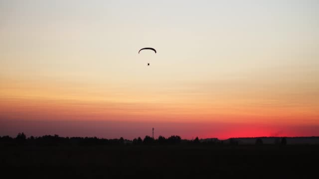 The-pilot-on-a-paraglider-flies-from-the-camera-gradually-moving-away-into-the-distance-against-the-sunset-beautiful-sky-Beautiful-background-background-picture-concept-of-freedom