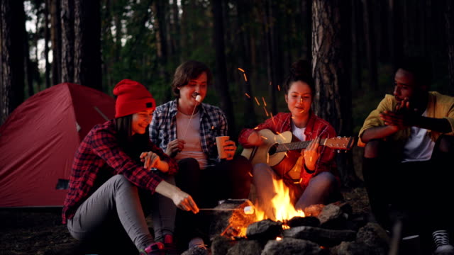Happy-adventurous-hikers-are-sitting-around-fire-singing-and-playing-the-guitar-eating-marshmallow-and-clapping-hands-on-dark-summer-evening-Tent-in-forest-is-visible-