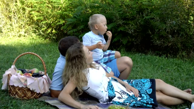 Family-picnic-in-the-Park-Mom-and-dad-lie-on-the-grass-and-the-happy-little-son-sits-on-top-of-them-and-eats-grapes-