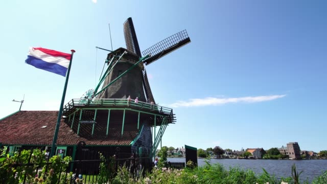 Tourist-couple-taking-pictures-of-traditional-Windmills-at-the-Zaanse-Schans-near-Amsterdam-Holland