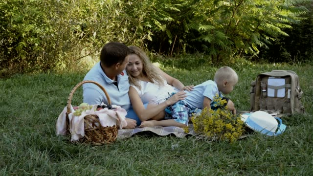 Happy-family-had-a-picnic-in-nature-Mom-dad-and-little-son-lie-and-play-on-the-grass-in-the-Park-