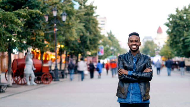 Time-lapse-of-smiling-African-American-man-standing-alone-in-city-center-with-hands-crossed-enjoying-city-life-and-looking-at-camera-Youth-and-lifestyle-concept-