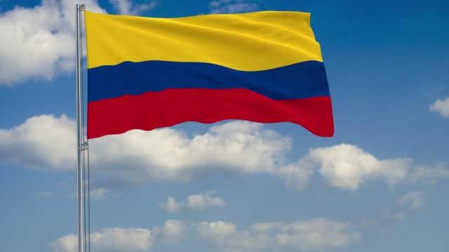 Flagge-Kolumbiens-vor-Hintergrund-Wolken-am-blauen-Himmel-schweben