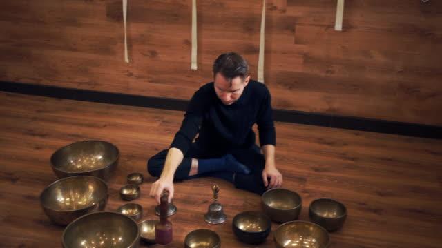 Un-hombre-se-sienta-en-la-posición-de-loto-y-juega-en-los-cuencos-cantores-tibetanos