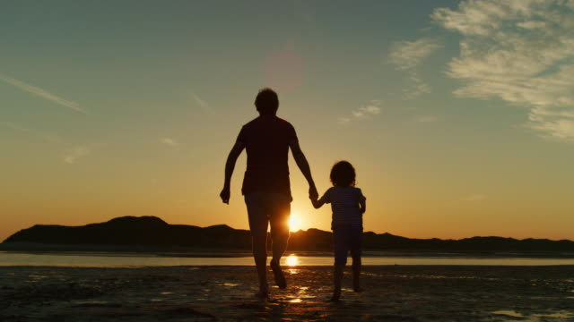 Silhouette-Of-Father-And-Son-Running-Together-At-Beach