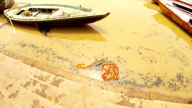 Las-escaleras-de-la-guirnalda-funeraria-smashan-y-las-brasas-negras-flotan-en-botes-sagrados-del-río-Ganges-en-el-muelle