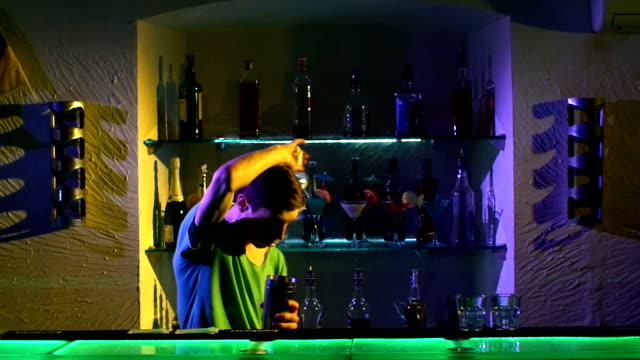 Professional-barman-making-cool-amazing-tricks-using-shaker-and-bottle-juggling-standing-behind-the-bar-catching-throwing-up-imitation-slow-motion