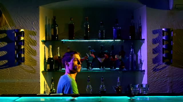 Professional-barman-making-cool-amazing-tricks-using-three-shakers-juggling-standing-behind-the-bar-catching-throwing-up-slow-motion