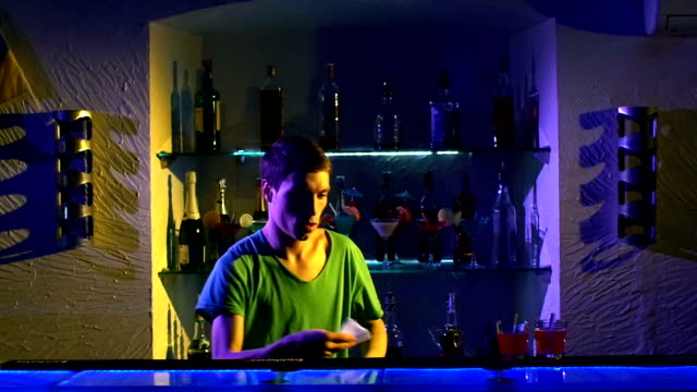Professional-barman-using-bottle-standing-behind-the-bar-serving-and-mixing-cocktail-slow-motion