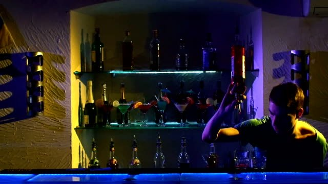 Professional-barman-making-cool-amazing-tricks-using-bottle-juggling-standing-behind-the-bar-catching-throwing-up-and-pouring-slow-motion