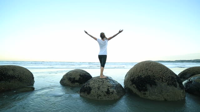Female-exercises-yoga-on-a-boulder-by-the-sea