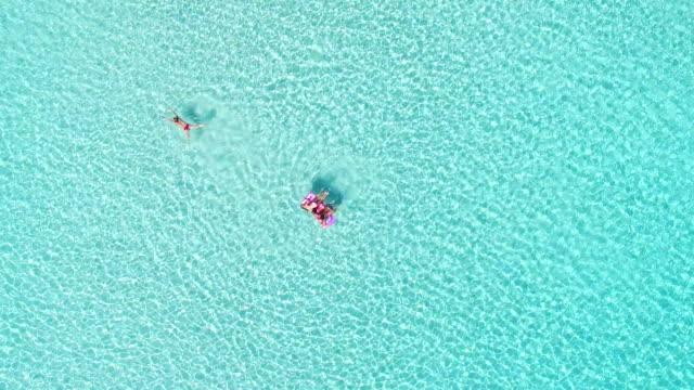 Atractiva-mujer-nadando-junto-a-los-niños-en-un-colchón-inflable