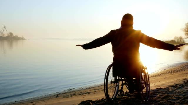 paralizar-las-manos-de-la-persona-para-arriba-en-silla-de-ruedas-sola-desactivada-en-la-puesta-del-sol