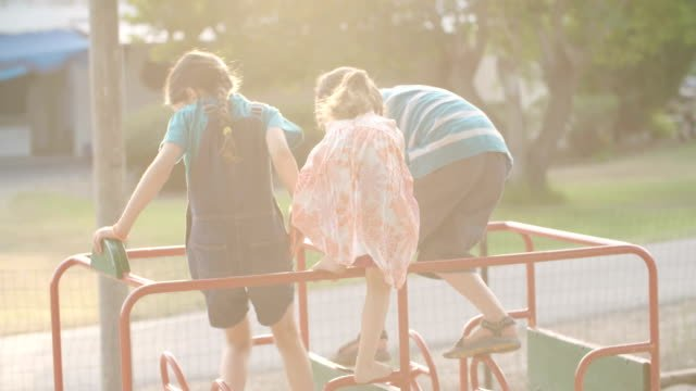 Three-kids-playing-in-a-public-playground-during-sunset