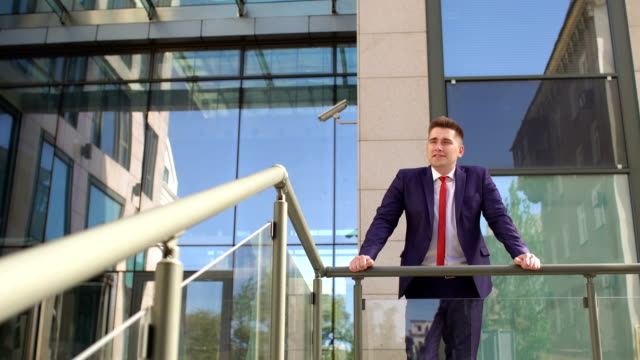 Businessman-is-leaning-on-railing-near-building-