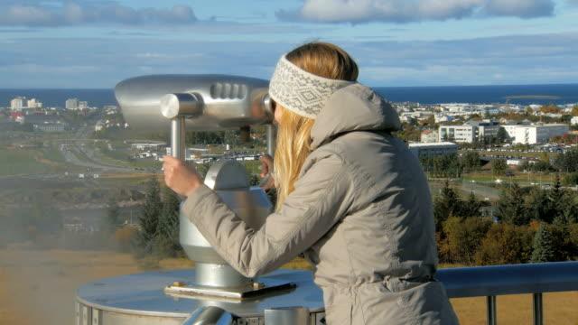 chica-joven-turista-está-buscando-en-un-telescopio-estacionario-en-Reikiavik-en-día-soleado