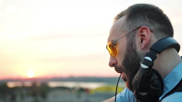 Perfil-de-moda-DJ-con-auriculares-y-gafas-de-sol-disfrutando-de-la-música-en-la-fiesta-de-verano-en-la-azotea