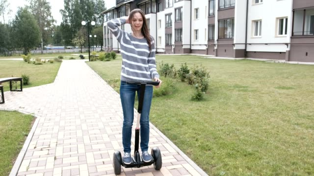 Beautiful-brunette-woman-is-rolling-on-gyro-scooter-near-the-home-