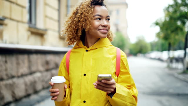 Happy-African-American-woman-is-using-smartphone-touching-screen-and-smiling-walking-outdoors-in-beautiful-city-with-to-go-coffee-Modern-lifestyle-and-communication-concept-