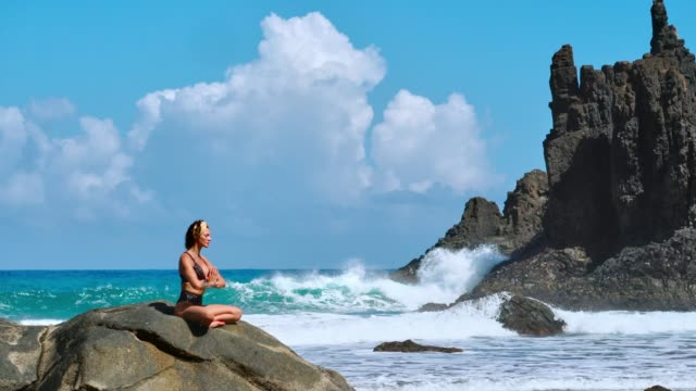 Yoga-de-meditación-Serena-Mujer-turista-morena-meditando-en-posición-de-loto-sobre-promontorio-sobre-la-pintoresca-Praia-da-Marinha-Mujer-meditando-sobre-los-acantilados-de-las-Islas-Canarias