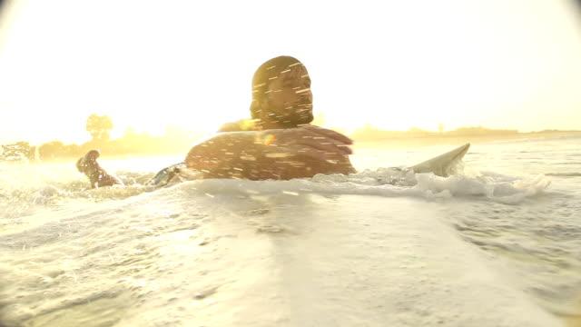 SLOW-MOTION:-Surfer-paddling-at-sunset-in-Sri-Lanka