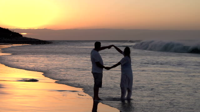 Couple-enjoying-romantic-embrace-on-the-beach-in-silhouette-South-Africa