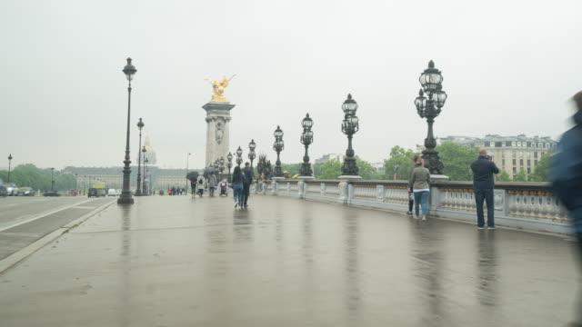 Gente-caminando-sobre-el-puente-de-Alexandre-III-en-un-día-rainny