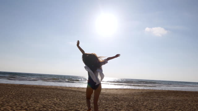 Young-woman-running-on-beach-to-the-ocean-at-sunset-and-raised-hands-Beautiful-young-girl-going-on-sandy-shore-to-the-sea-and-enjoying-freedom-during-vacation-Relax-on-summer-holiday-Rear-back-view