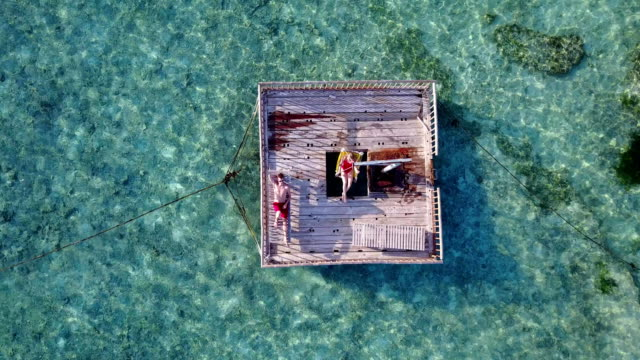 v03858-Aerial-flying-drone-view-of-Maldives-white-sandy-beach-2-people-young-couple-man-woman-relaxing-on-sunny-tropical-paradise-island-with-aqua-blue-sky-sea-water-ocean-4k-floating-pontoon-jetty-sunbathing-together