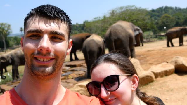 Young-smiling-couple-doing-selfie-photo-with-elephants-in-surroundings-of-reserve-in-Sri-Lanka