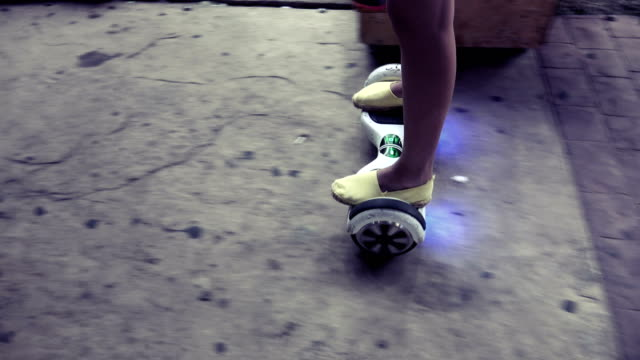 Girl-ride-on-electrical-scooter-hoveboard-at-night-on-walkway