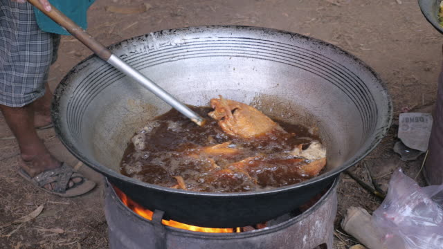 Close-up-of-a-man-taking-fried-fish-out-of-a-large-wok-cooking