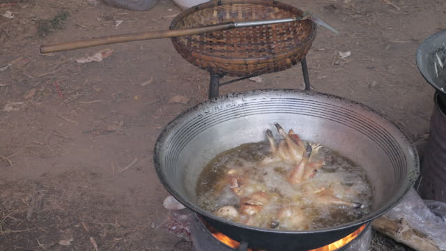 Deep-frying-chickens-in-a-large-wok-cooking-on-a-charcoal-and-wood-brazier-stove-outdoors
