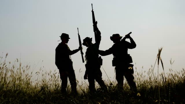 Silueta-de-tres-completamente-equipados-y-armados-soldados-de-pie-en-el-campo-de-batalla-después-de-la-guerra-