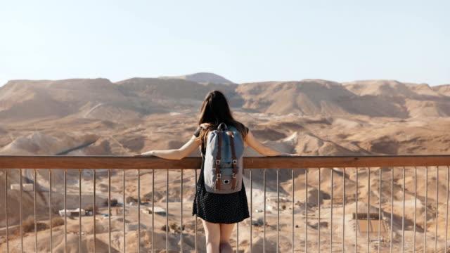 Chica-se-encuentra-en-gran-vista-a-la-montaña-amplia-los-brazos-abiertos-Mujer-Europea-bastante-feliz-y-emocionada-Libertad-Masada-Israel-4K