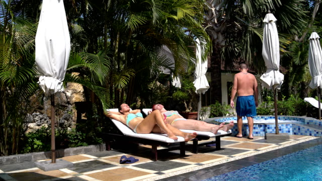 Two-women-sunbathing-on-the-sun-loungers-around-the-pool-A-man-walks-into-a-hot-tub
