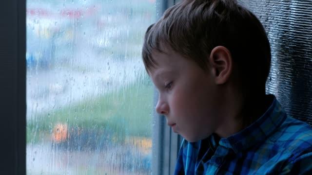 Niño-mira-por-la-ventana-la-lluvia-y-es-triste.