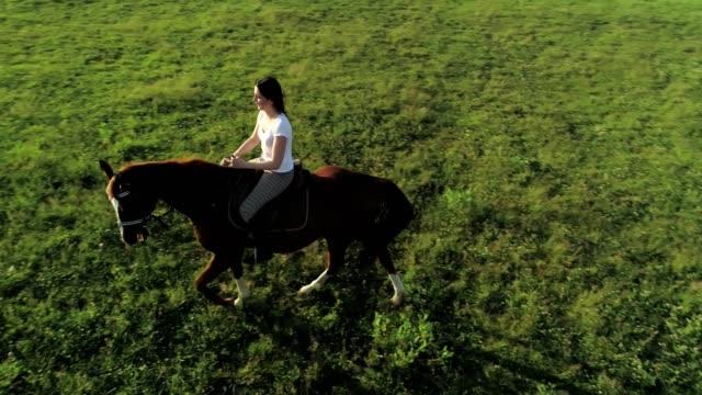 Una-mujer-joven-cabalga-un-caballo-marrón-vista-aérea-cámara-lenta-objeto-que-se-mueve-lejos-de-la-cámara