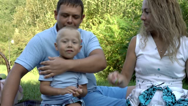 Happy-mom-sits-and-feeds-grapes-to-her-little-son-and-his-dad-on-the-grass-in-the-Park-A-woman-laughs-and-kisses-a-man-Family-picnic-in-nature-