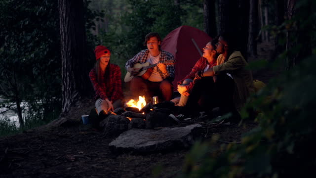 Cheerful-travelers-are-singing-songs-and-playing-the-guitar-sitting-around-fire-in-forest-in-the-evening-and-having-fun-with-beautiful-nature-around-People-and-music-concept-