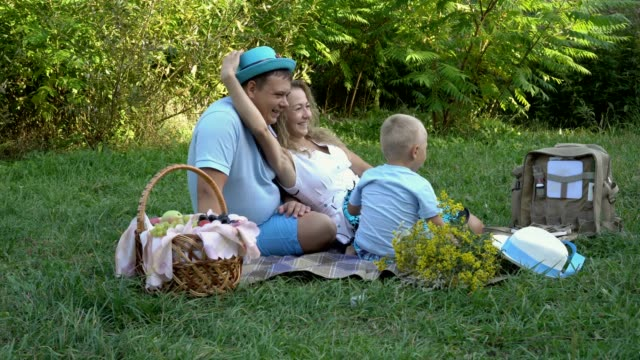 The-family-had-a-picnic-in-nature-Mom-dad-and-little-son-having-fun-and-playing-with-hats-on-the-grass-in-the-Park-