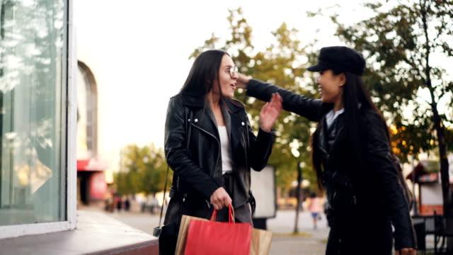 Chica-atractiva-es-elegir-ropa-de-tienda-ventana-permanente-al-aire-libre-y-reuniones-a-amiga-mujeres-jóvenes-son-abrazos-discutiendo-las-cosas-en-bolsas-de-papel-y-dejando-