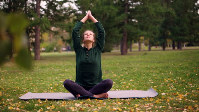 Chica-guapa-está-sentado-en-posición-de-loto-sobre-la-estera-de-yoga-en-pasto-en-el-parque-de-la-ciudad-cogidos-de-la-mano-de-namaste-en-mudra-sobre-las-rodillas-y-respirar-Concepto-de-meditación-y-de-la-naturaleza-