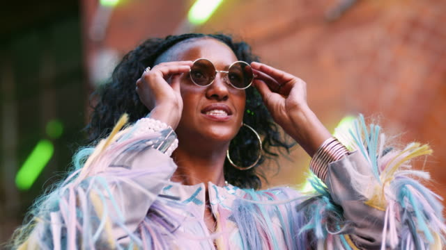 Young-black-woman-wearing-multicoloured-fringed-jacket-putting-on-sunglasses-low-angle-head-and-shoulders