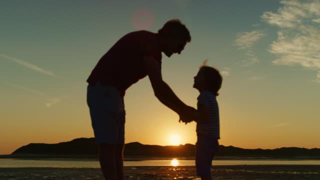 Silhouette-von-Vater-und-Sohn-spielen-zusammen-am-Strand-