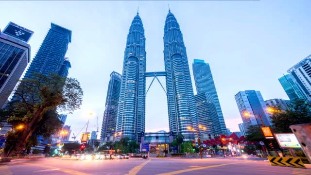 De-la-noche-al-día-4-K-time-lapse-of-intersección-semáforo-en-frente-de-Suria-KLCC-con-torres-Petronas-