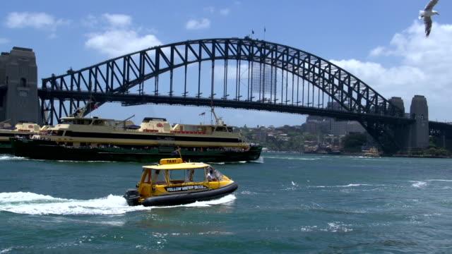 Big-ferries-y-una-pequeña-taxi-acuático-y-pase-por-el-puente-del-puerto-de-Sydney