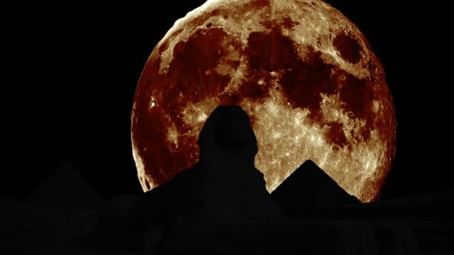 Silhouetten-von-der-Sphinx-und-die-Pyramiden-mit-riesigen-Mond